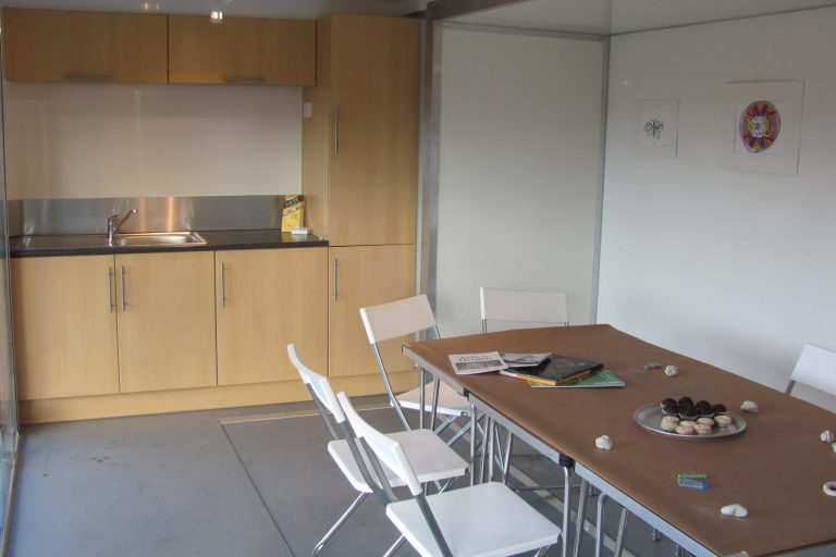 Hospitality trailer interior with table and kitchen units