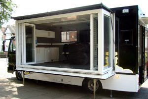 gull wing extension on a vehicle with open sides for use as stage