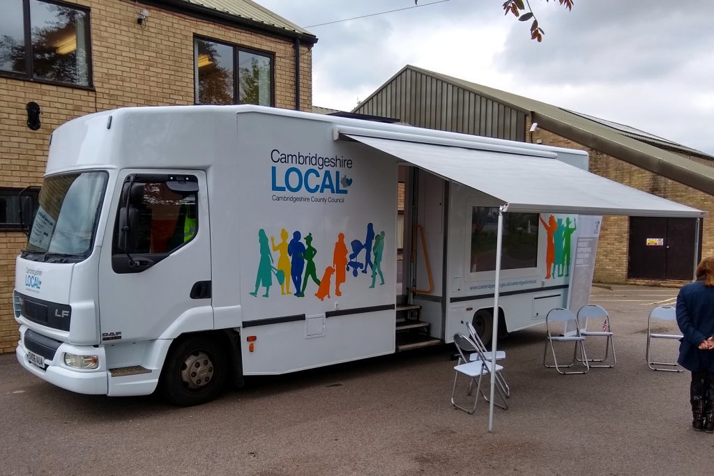 external view of a large outreach vehicle which features a large screen fitted to the body, a wind out awning and anentrance door with integral wheelchair lift