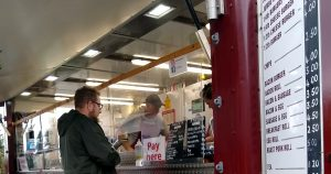 male customer waiting to be served at a burger van trailer