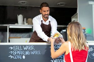 youn lady being served a burger from a catering trailer