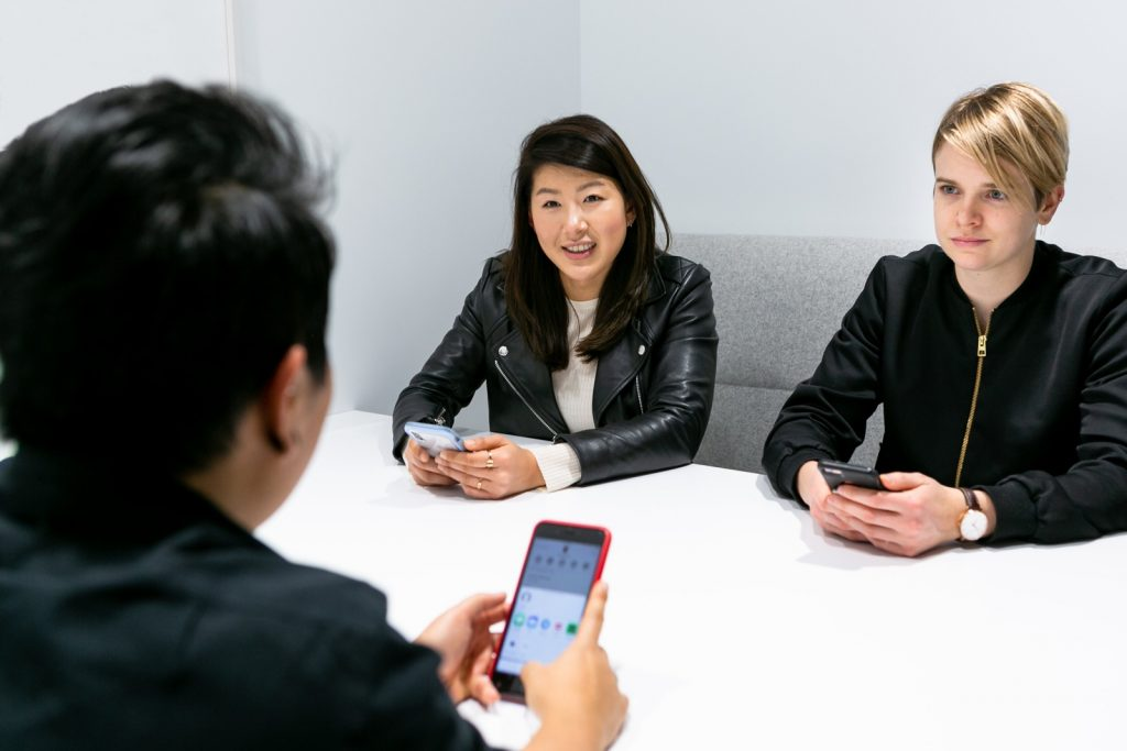 two recruitment staf interviewing a man for a job whilst sitting around a table
