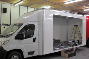 a chassis cab vehicle in build showing a box body with side cut out