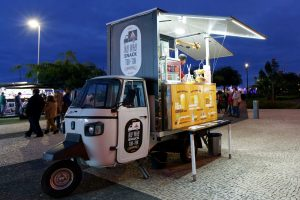 a small food truck with counter open in a dark evening