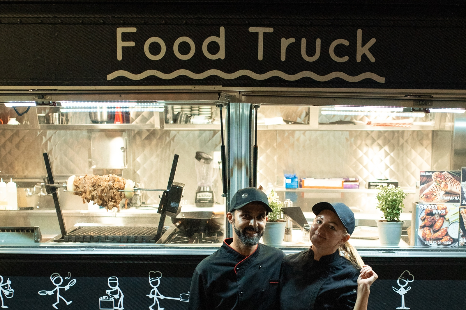 the counter of a food truck with two of the serving staff standing outside in front of the counter smiling